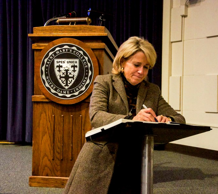 Saint Mary's president Jan Cervelli signs the It's On Us pledge to work towards ending sexual assault on college campuses at the town hall forum Monday night.