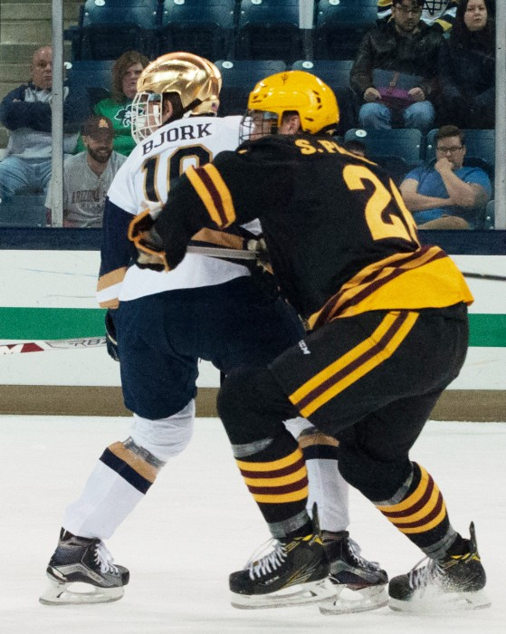 Junior forward Anders Bjork holds off a defender during Notre Dame's 4-2 win over ASU on Saturday at Compton Family Ice Area.