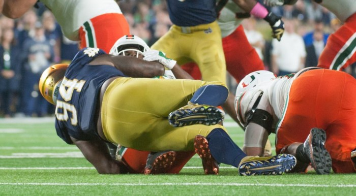 Irish graduate student defensive lineman Jarron Jones swallows Miami sophomore running back Mark Walton in the backfield during Notre Dame's 30-27 victory over the Hurricanes at Notre Dame Stadium. Jones finished with seven total tackles — six of them for a loss, including one sack — and one pass break up in the win.