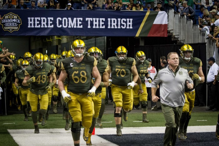 Notre Dame players and head coach Brian Kelly, right, run onto the field before Notre Dame's 44-6 win over Army on Saturday at the Alamodome.