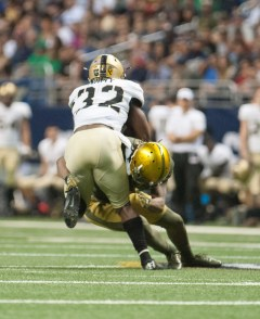 An Irish defender makes a tackle against an Army ball carries.