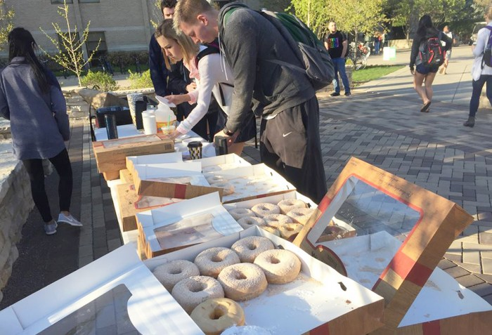 Students eat Rise'n Roll Bakery doughnuts outside of DeBartolo Hall on Monday as part of the week-long AnTostal celebration.