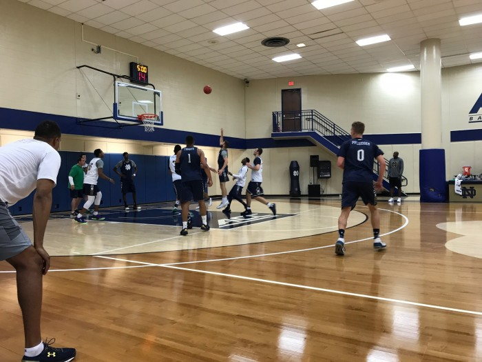 Irish assistant coach Ryan Ayers looks on as sophomore forward Nikola Djogo gets up a runner in a practice on July 6 at the JACC.