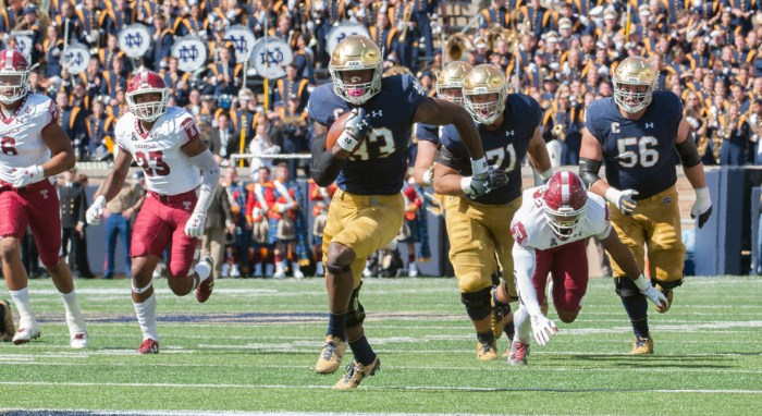 Irish junior running back Josh Adams protects the ball while running up the field in Notre Dame's 49-16 victory over Temple on Saturday at Notre Dame Stadium. Adams rushed for 161 yards and two touchdowns in the game. Adams has 1,929 total rushing yards in his collegiate career and holds Notre Dame's single-game rushing record for a freshman.