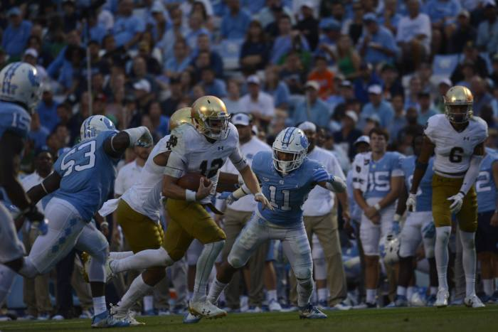 Irish sophomore quarterback Ian Book breaks through the line of scrimmage during Notre Dame's 33-10 win over North Carolina on Saturday at Kenan Memorial Stadium in Chapel Hill, North Carolina.