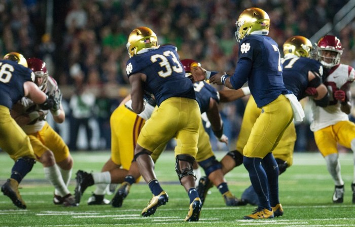 Irish junior running back Josh Adams, left, accepts the handoff from junior quarterback Brandon Wimbush during Notre Dame's 49-14 win over USC on Saturday at Notre Dame Stadium.