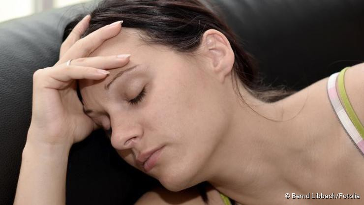 Frau hält leidend ihren Kopf