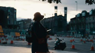 Frau mit Handy vor urbanem Hintergrund, geparktes Moped