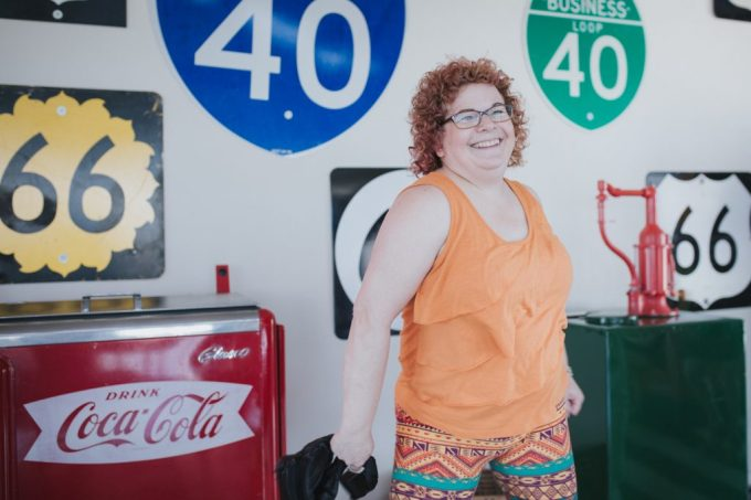 A woman smiling by old highway signs and a coke machine