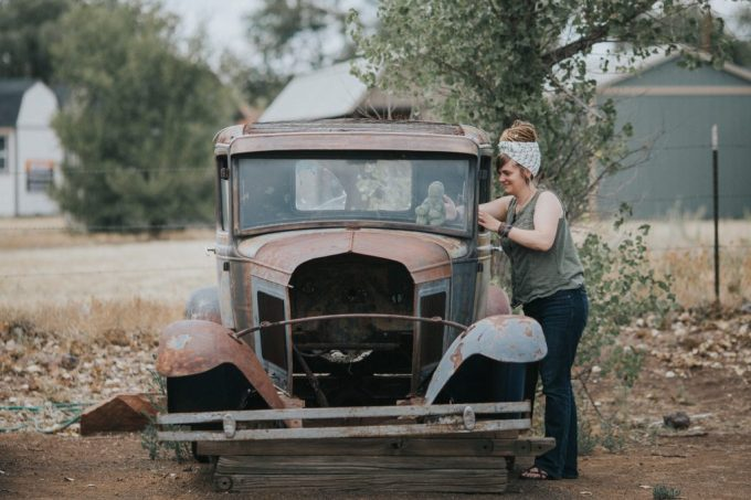 A woman places a stuffed animal inside an old, rusty car