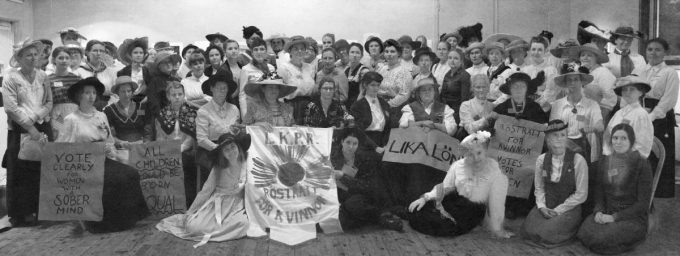 Dozens of suffragette characters holding signs and posing