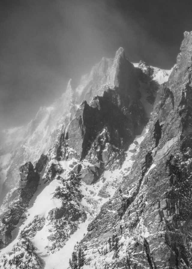This is a harsh black and white photograph of a winter landscape. The jagged edges of the mountain match well with the intensity of the cold weather conditions.