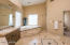 Master bathroom features custom tile, double sinks, vanity, separate shower & tub, walk-in closet