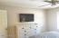 Flat screen TV on bedroom wall