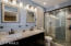 REMODELED MASTER BATHROOM HAS A TILED WALK-IN SHOWER AND DUAL VANITY SINKS
