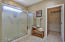Large master bath with large shower and seat, travertine floor, and double sinks. Travertine also in closet.