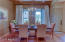 Dining room with custom window treatments and rods.