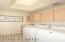 Laundry room with utility sink, plenty of storage cabinets & skylight