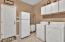 Huge laundry room has cabs, sink , fridge!