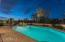 Professionally landscaped yard with strategically placed landscaped lights and a sparkling lit pool create a fantastic night scene.