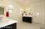 Spacious master bathroom features double vanities.