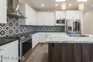 Huge kitchen featuring leathered Granite topped island and Slate Grey Quartz. Samsung smart appliances.