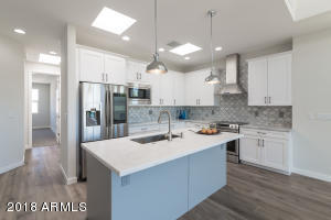 Honed Carrara Marble tops with Leathered Opal White Granite island. Grey and white custom cabinets. Samsung smart appliances.