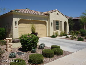Former Model home front with mature landscapping plants and trees.