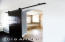 Custom barn door leads to designer remodeled master bathroom