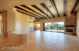 Great room with gas fireplace, 20x20 tile, stone, and wood beams