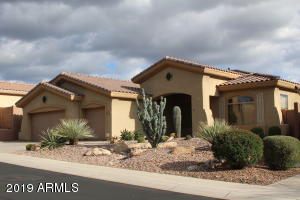 Front of home with north/south exposure and desert landscape.