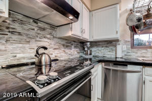Sparkling s/s, granite and tile in the kitchen with a s/s pot rack above the kitchen sink.