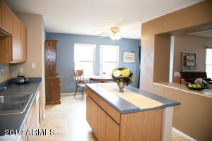 Bright kitchen open to dining and peek through to living room