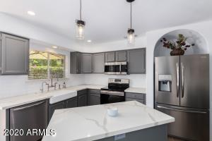 Calcutta marble countertops and island. Ceiling remodeled from fluorescent insert to can lighting & modern fixtures.