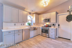 This highly upgraded Kitchen is open and features gray cabinetry with brushed nickel hardware, stainless farmhouse sink , gas cook top with 4 burners and a griddle, quartz counters, and white subway tile backsplash.