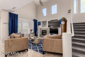 Open living room boasts fireplace, new polished travertine floors and vaulted ceilings.
