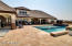 Salt water pebble Tech pool with a large baja deck, two umbrella sleeves, shaded sitting area, and water features.