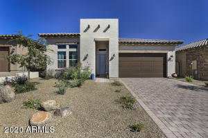 Single story gated Tonto Verde home with paver driveway and beautiful desert landscaping