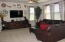 Neutral Great Room offers tall windows, ceiling fan & like new carpeting