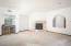 Spacious family room with fireplace and bar area with a wine fridge.