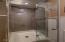 Tiled standup shower with glass door.