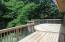 Huge deck overlooks level back yard & woods. Enter from kitchen or family room - stairs to patio below.