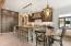 Center island kitchen includes custom designed live-edge wood table and stone range hood