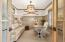 Study features wainscoting and reclaimed wood doors