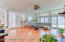 Large sunken family room off kitchen with glistening hardwood flooring, recessed lighting, and ceiling fan