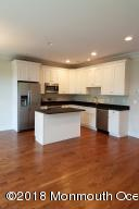 White shake style cabinetry with granite tops and a center island
