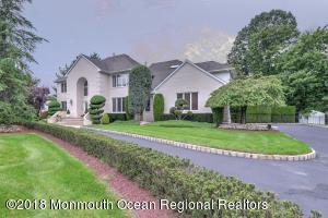 Full brick front, custom colonial in Northern Manalapan with circular driveway.