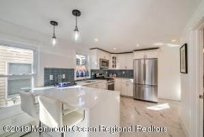 quartz peninsula with pendant lighting, note French door stainless fridge, builtin microwave, porcelain tile and more.