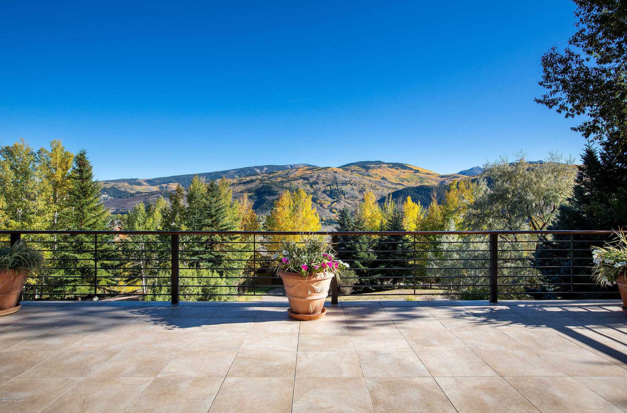 Perched atop Singletree on a quiet cul-de-sac is this contemporary home with awe-inspiring mountain and ski slope views and even a glimpse of Arrowhead's golf course. The home's prominent water feature greets you upon entry and leads you to the large and completely open living and dining space featuring gas fireplace and heated hearth, vaulted ceilings and striking sliding glass, nano doors that beckon you to the impressively large patio. For your cooking convenience, enjoy the induction range, convection oven, 2 dishwashers and island with second sink and bar stools. The main level also includes entry from the oversized 3-car garage, laundry room, mud room with heated bench, the first of 2 offices, powder room, junior master suite and elevator to each floor. The home's upper level houses a private master suite complete with balcony, beautiful 5-piece bath and large second office perfect for today's work-from-home culture. The lower level includes a second, walk-out living space with nano doors leading to another large patio and the flat, grassy yard, wet bar, 2 guest bedrooms and bathrooms, and a large, heated storage room. This home was designed and constructed with environmentally friendly products and its notable features include marble, granite and porcelain finishes throughout, alderwood doors and trim, Lutron lighting control system, energy recovery ventilator and ample parking.