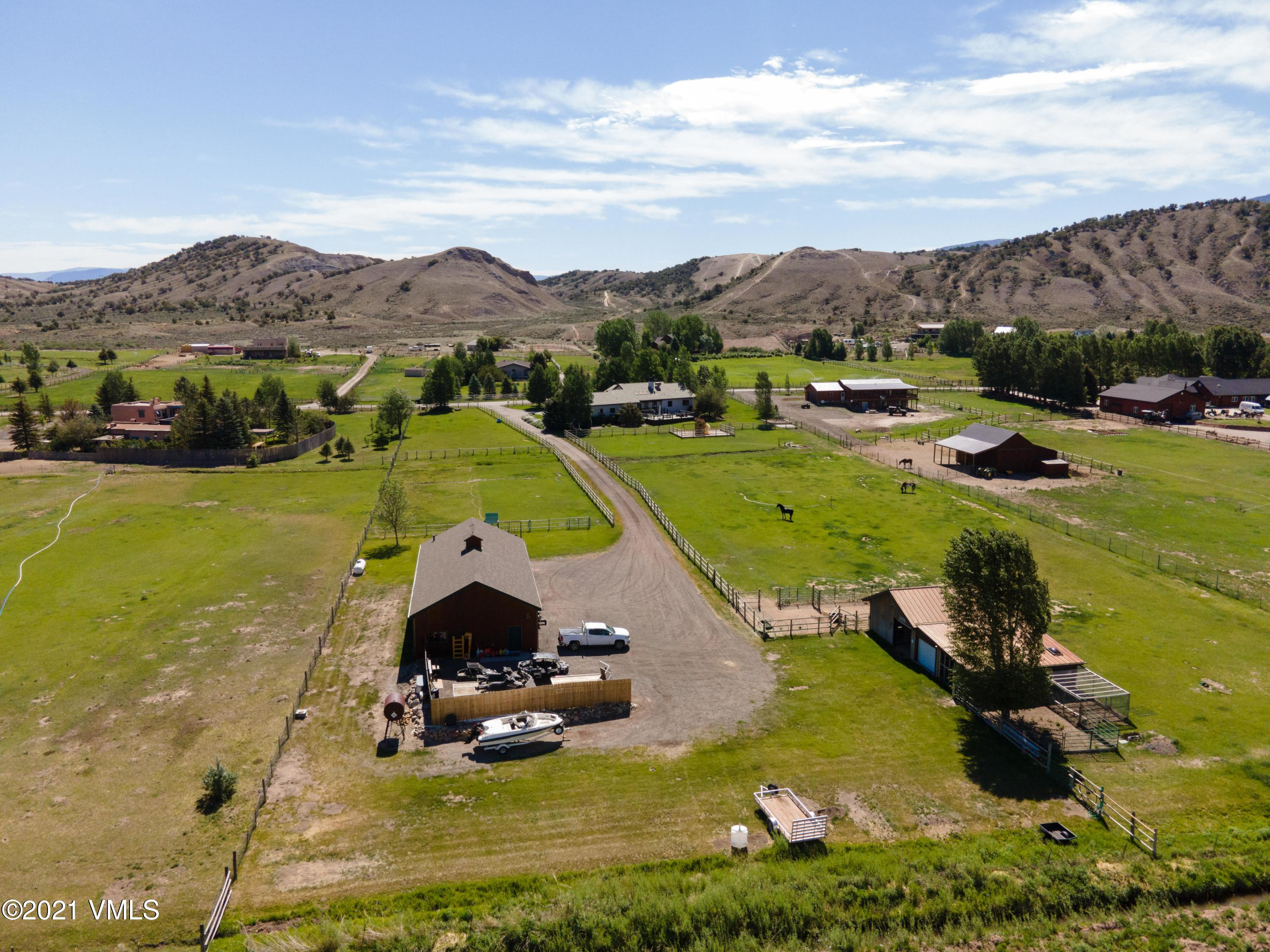 Custom home on 4 acres, Features include 5 bed, 4.5 baths, oversized 3 car garage, 2100 sq.ft. 3-bay shop.  The grounds are meticulously maintained and provide a horse and livestock turn-key opportunity complete with a horse barn with 2 stalls, tack room, chicken coop, fenced and irrigated pastures, deeded water rights.  Beautifully appointed home with high end appliances and finishes, main floor master, maintenance free exterior, in-floor radiant heat and air conditioning. The large deck and backyard are an entertaining paradise with incredible southerly mountain views.   Low maintenance stucco exterior and lifetime roof.